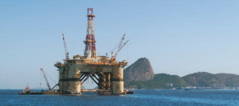 An offshore oil rig is pictured on the water with a landscape of hills in the background.